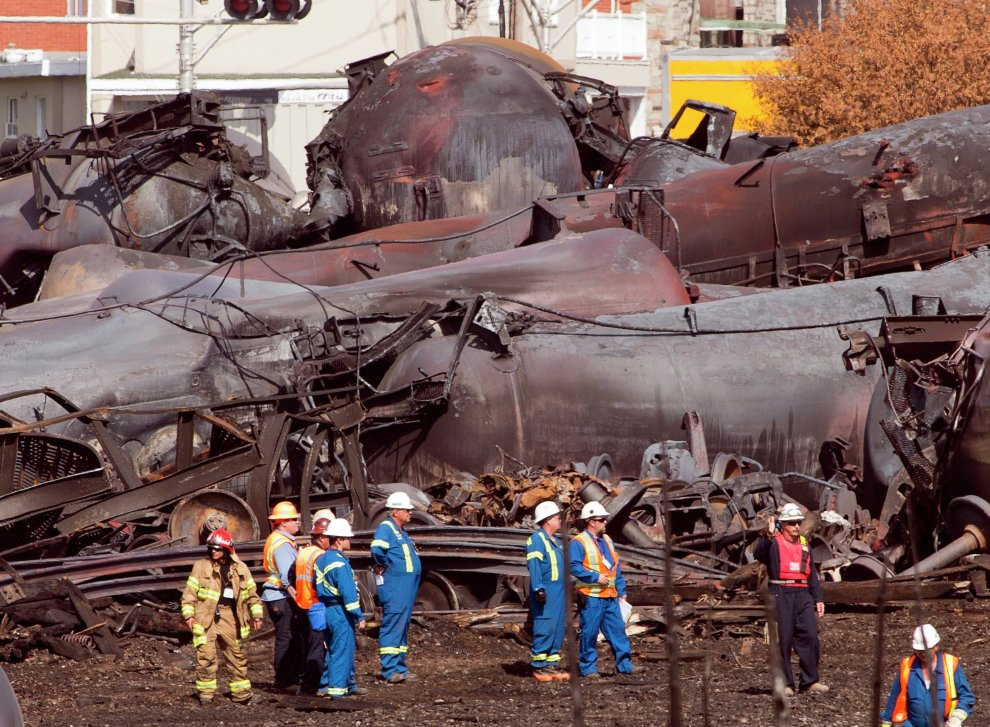 In this July 6, 2013, file photo, workers stand before mangled tanker cars at the crash site of the train derailment and fire in Lac-Megantic, Quebec, Canada.