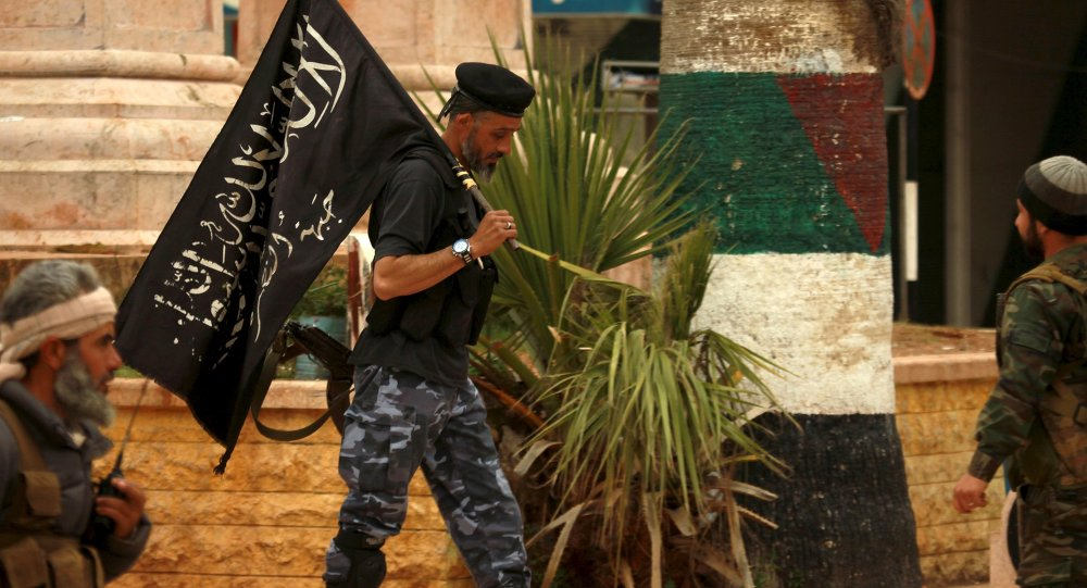 A Nusra front fighter carries his brigade's flag in Idlib city, after they took control of the area March 29, 2015