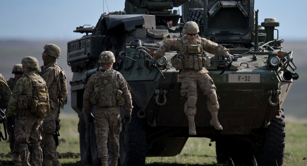 US Army serviceman jumps from armored vehicle during the NATO Wind Spring 15 military exercise at Smardan military shooting range on April 21, 2015