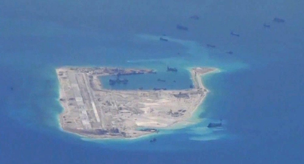 Chinese dredging vessels are purportedly seen in the waters around Fiery Cross Reef in the disputed Spratly Islands in the South China Sea in this still file image from video taken by a P-8A Poseidon surveillance aircraft provided by the United States Navy
