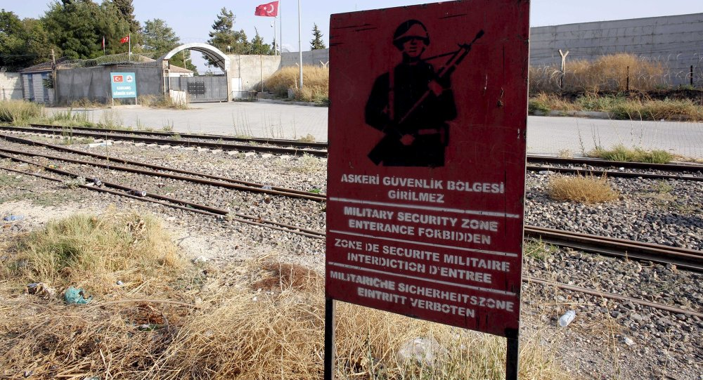 A Turkish military warning sign, with the closed Karkamis border gate in the background, is pictured in Karkamis, bordering with the Islamic State-held Syrian town of Jarablus, in Gaziantep province, Turkey