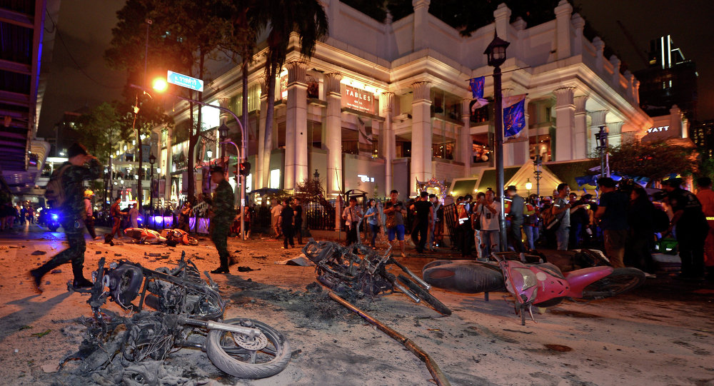 Thai soldiers inspect the scene after a bomb exploded