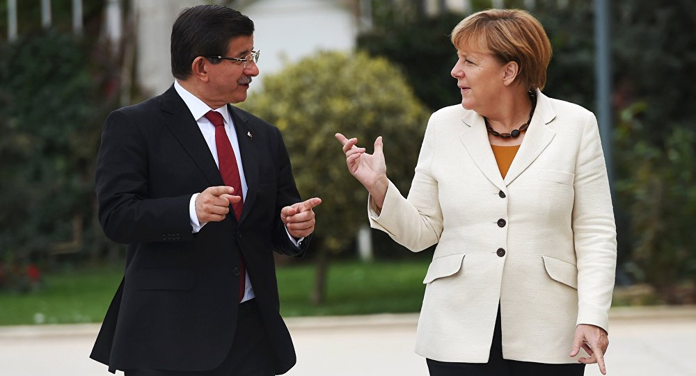 Turkish Prime Minister Ahmet Davutoglu (L) and German Chancellor Angela Merkel chat during their meeting in Istanbul, Turkey