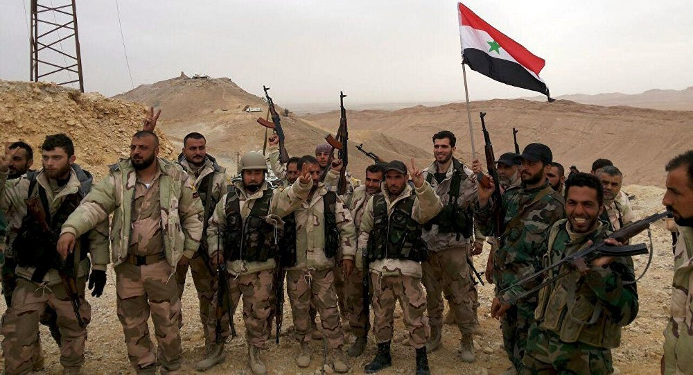 Forces loyal to Syria's President Bashar al-Assad flash victory signs and carry a Syrian national flag on the edge of the historic city of Palmyra in Homs Governorate, in this handout picture provided by SANA on March 26, 2016.