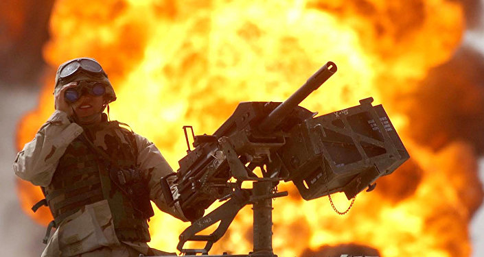 A US soldier looks through a pair of binoculars as a fire in the Rumeila oil field burns in the background in southern of Iraq, Sunday, March. 30, 2003