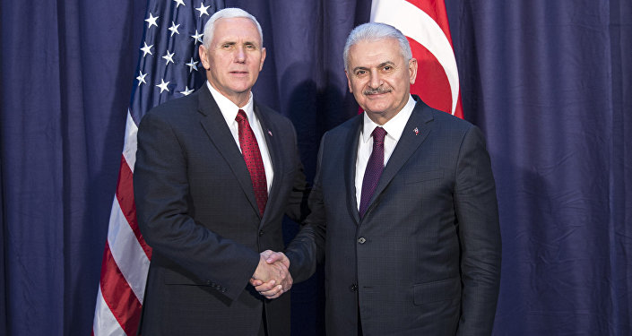 United States Vice President Mike Pence, left and Turkey's Prime Minister Binali Yildirim, right, shake hands for the photographers prior to their meeting during the Munich Security Conference in Munich, Germany
