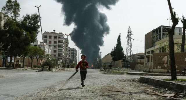 A child runs along a street in front of clouds of smoke billowing following a reported air strike on Douma, the main town of Syria's rebel enclave of Eastern Ghouta