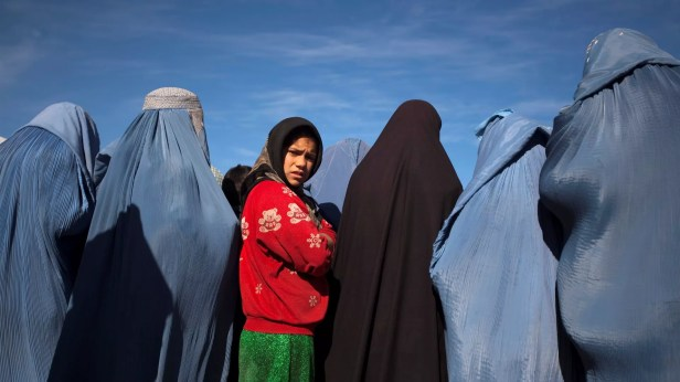 An Afghan girl stands among widows clad in burqas during a cash for work project by humanitarian organisation CARE International in Kabul - Sputnik International, 1920, 13.09.2021