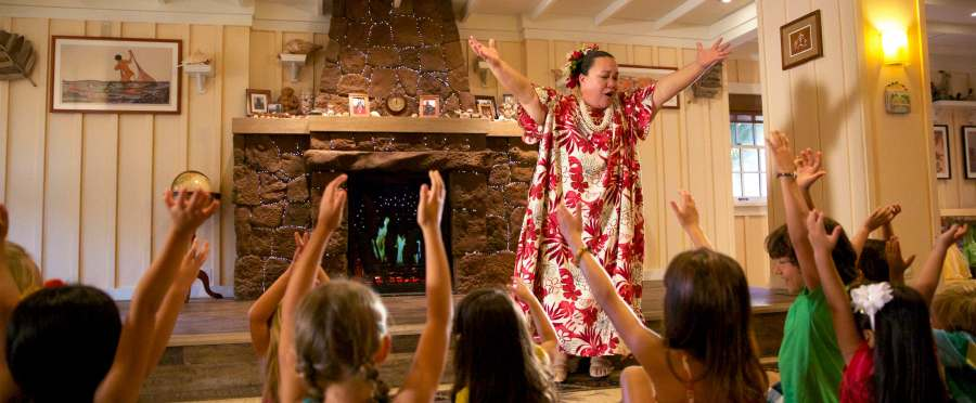 Aunty s Beach House   Kids Club   Aulani Hawaii Resort   Spa A woman in Hawaiian garb and a group of children sitting on the floor  watching her