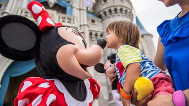 Minnie Mouse and young guest at Magic Kingdom Park