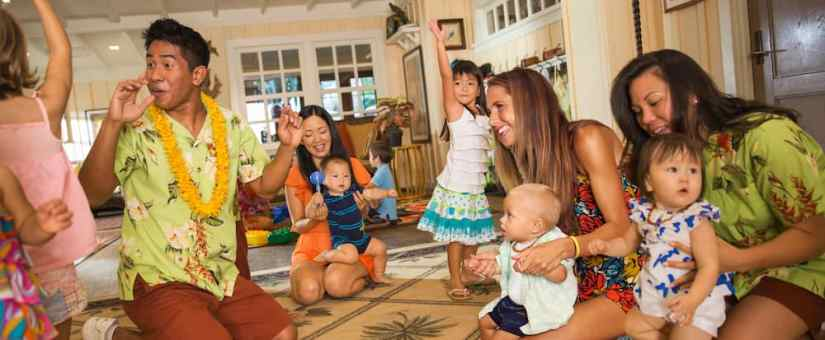 An enthusiastic Cast Member interacts with kids, infants and their mothers inside Aunty's Beach House