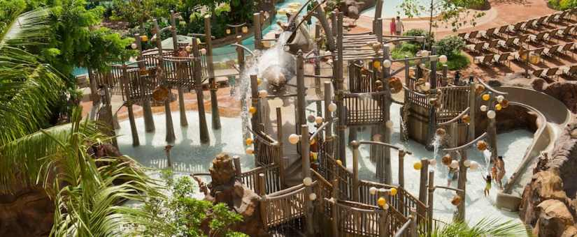 A mother and her children splash about in the water as other young Guests climb the Menehune Bridge