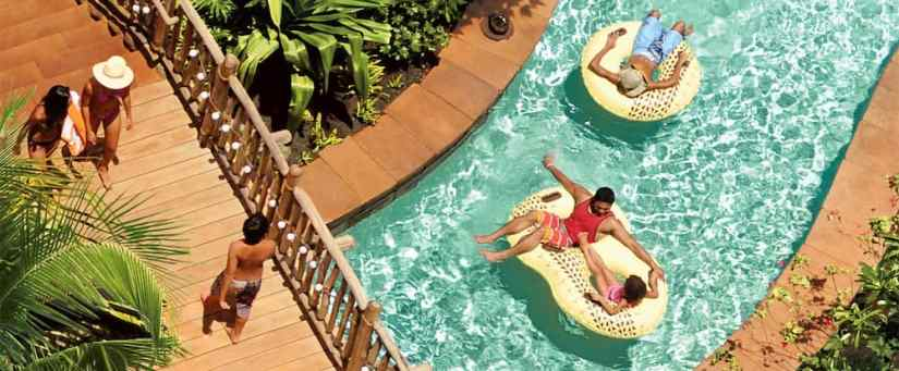 An overhead view of a bridge and a father and daughter on a 2-person inner tube floating down a lazy river