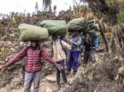 Porters balancing loads on Kilimanjaro
