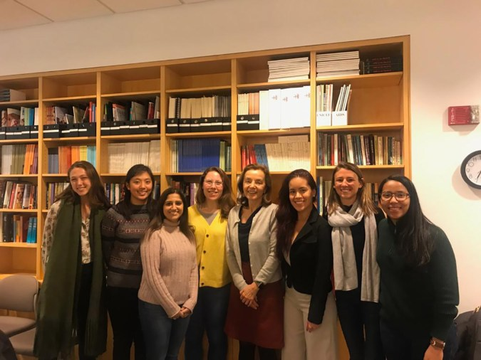 A group of smiling women in front of a bookcase
