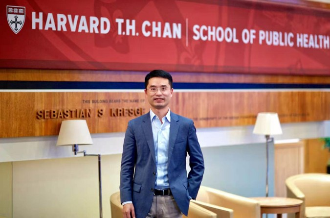 A student in a suit jacket inside Harvard Chan School