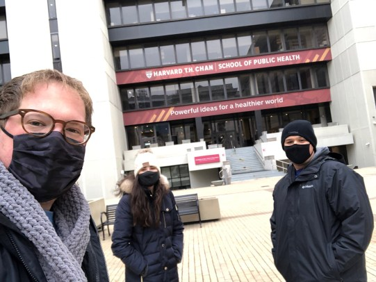 Students pose in front of Kresge courtyard in winter wearing masks