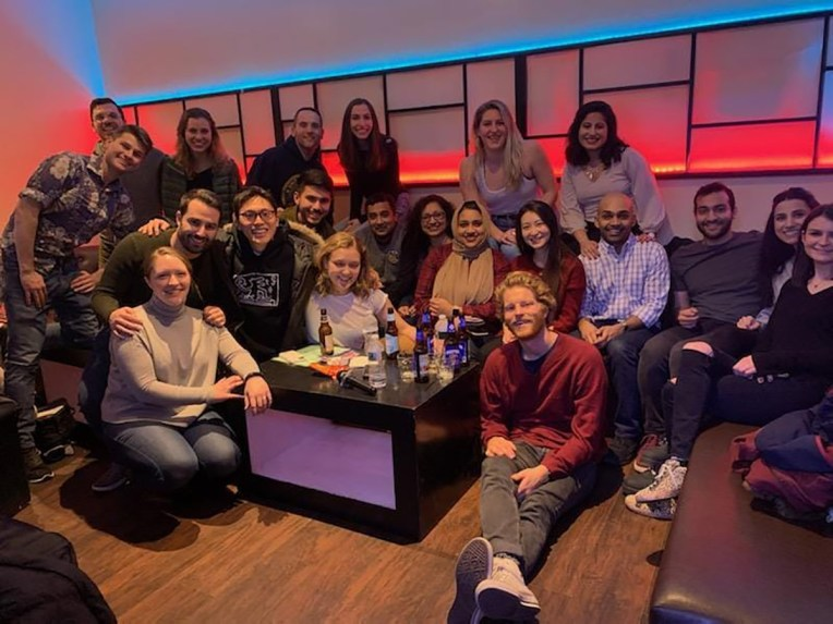A large group of students pose in a karaoke lounge before the pandemic