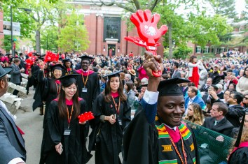 """Students at commencement in Cambridge holding """"wash hands"""" sign"""