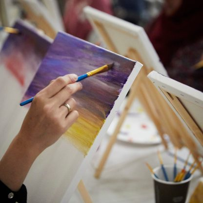 Student holding paintbrush to canvas