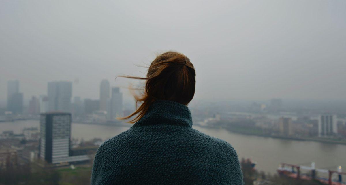 Una ragazza guarda il panorama di una città ricoperta dallo smog