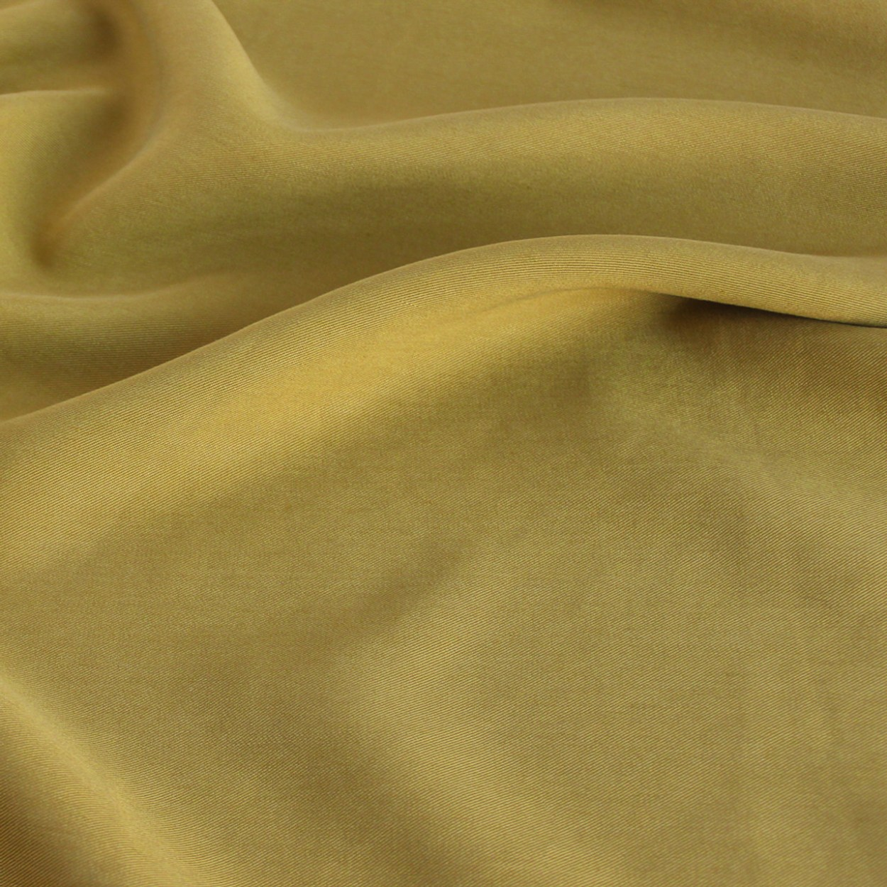A product photo of chartreuse tencel twill fabric, slightly rumpled to showcase the drape.