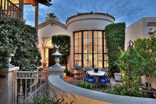house with metal gate and patio furniture