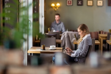 woman browsing on her computer in a coffee shop on the why every website owner should convert to https post