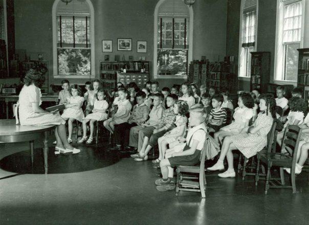 Teacher reading story to class of children