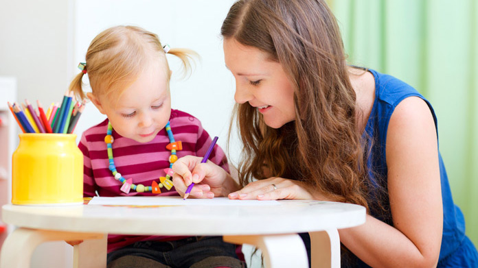 Woman sitting with a child drawing