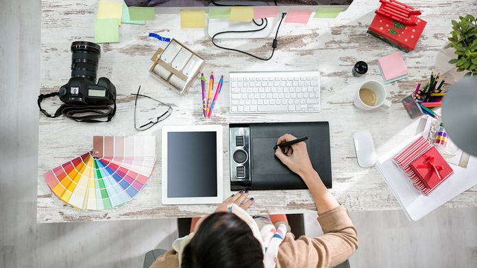 Woman drawing on a design pad, with various photography and design tools on her desk