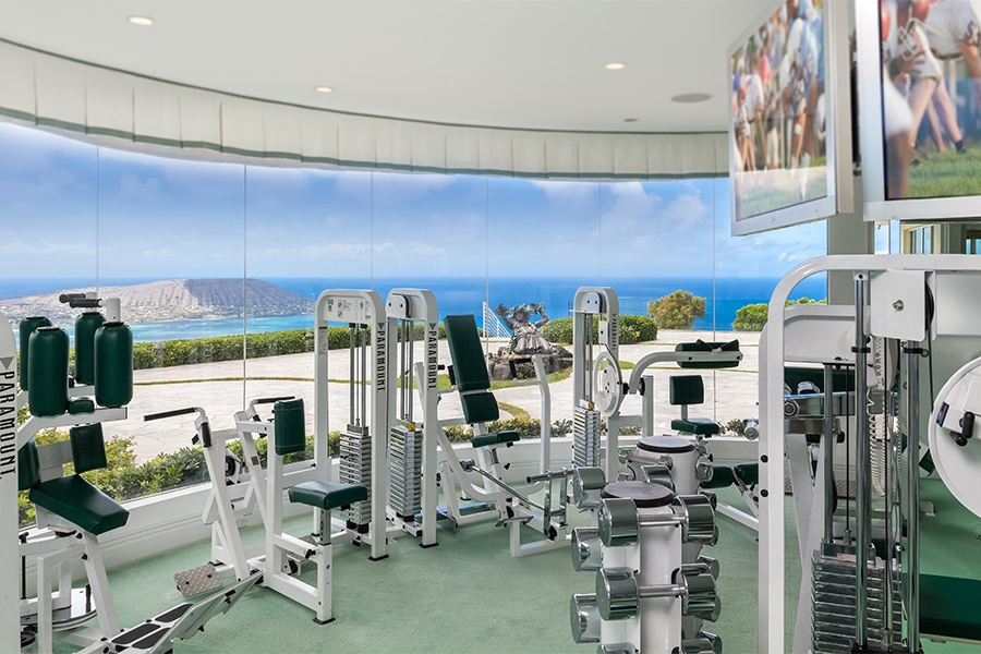 The fitness room of this glamorous Honolulu mansion boasts majestic panoramic views of the Pacific, enhancing the appeal of home workouts.