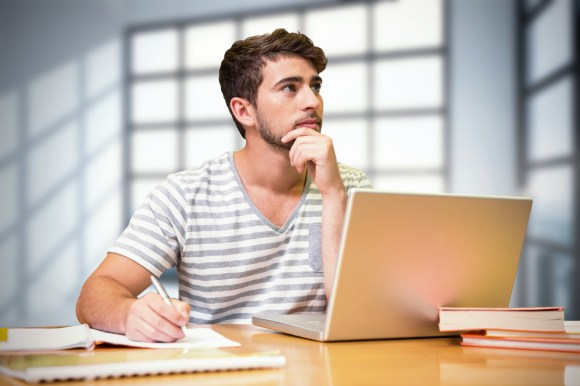 Student studying in the library with laptop against room with large windows showing city