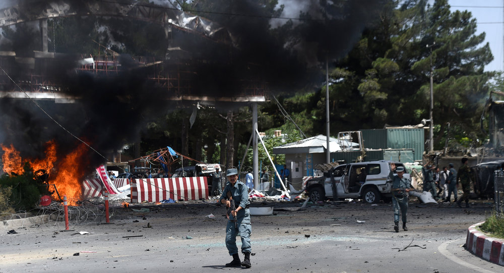 An Afghan policeman keeps watch at the site of a powerful truck bomb in Kabul on August 10, 2015