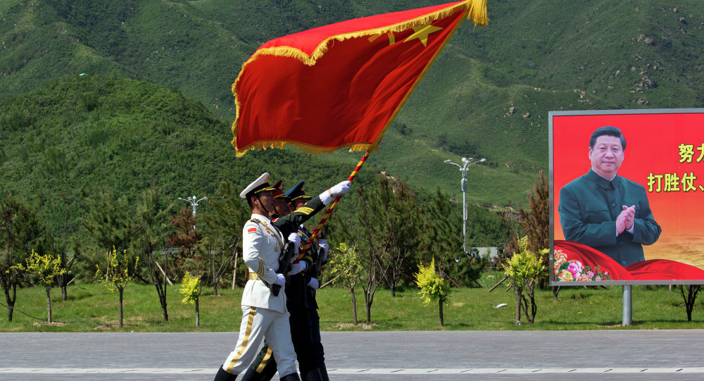 Chinese flag bearers practice marching near a portrait of Chinese President Xi Jinping ahead of a Sept. 3 military parade.