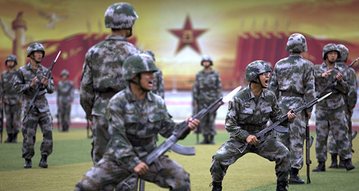 Chinese People's Liberation Army cadets shout as they take part in a bayonet drills at the PLA's Armoured Forces Engineering Academy Base, on the outskirt of Beijing, China Tuesday, July 22, 2014