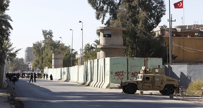 Iraqi security forces stand guard with their military vehicle outside the Turkish embassy in Baghdad December 8 2015