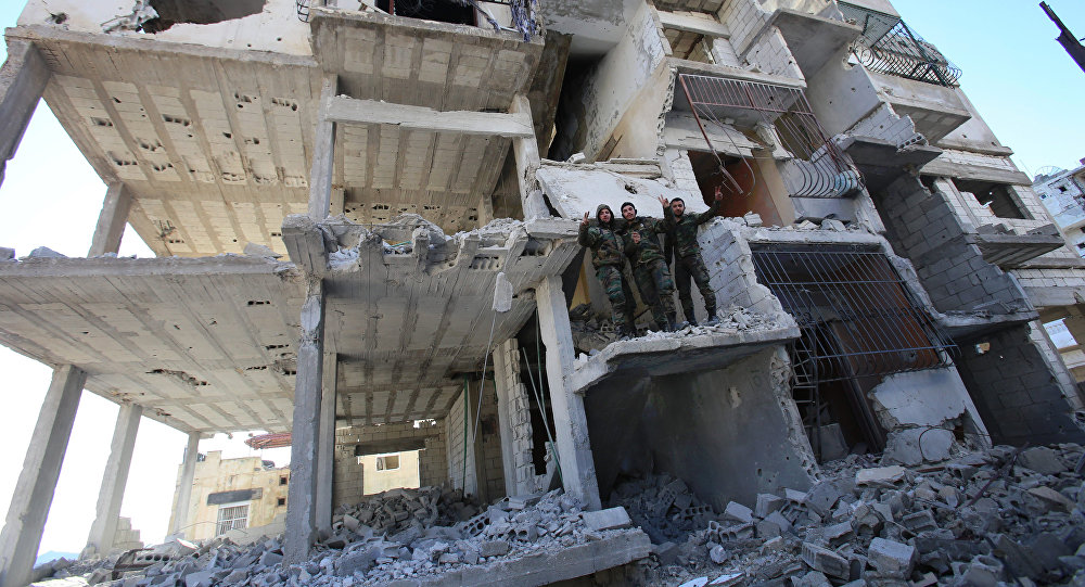 Members of the Syrian pro-government forces pose for a picture in a destroyed building in the strategic town of Salma, in the coastal Latakia province, on January 15, 2016, following its recapture from militants