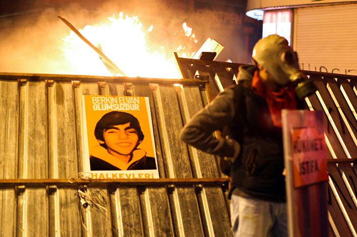 A protester stands in front of a barricade bearing a portrait of Berkin Elvan, the 15-year-old boy who died from injuries suffered during last year's anti-government protests, following clashes between police and demonstrators after the funeral of Elvan, in Istanbul on March 12, 2014.