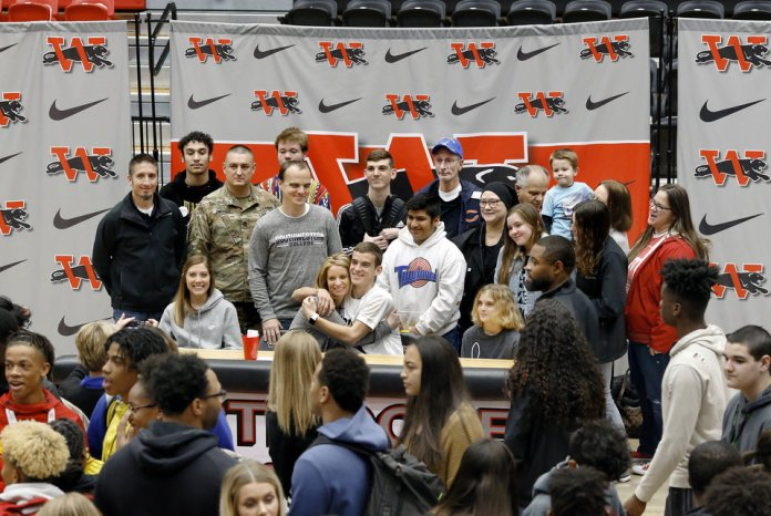 Photo - Jacob Vaughn poses with friends and extended family after all athletes had signed letters during Signing Day event at Westmoore High School on Wednesday, Feb. 6, 2019.  Photo by Jim Beckel, The Oklahoman.