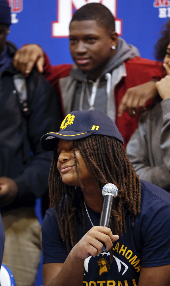 Photo - Millwood's Isaiah Major sits in front of his cousin OU signee Marcus Major during the signing ceremony for high school football players in the Millwood Field House in Oklahoma City, Wednesday, Feb. 6, 2019. Isaiah Major will play football at UCO. Photo by Nate Billings, The Oklahoman