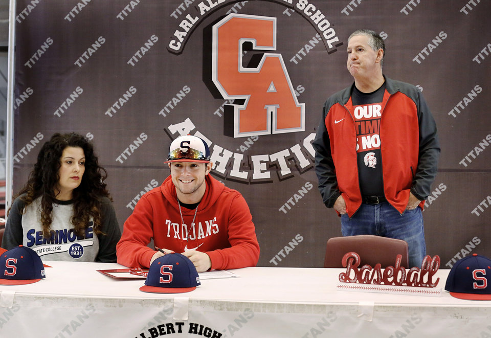 Photo - Carter LaValley is joined by his mom and Tim LaValley, his dad/coach, at a table where Carter signed a letter to play baseball at Seminole State College during Signing Day ceremony at Carl Albert  High School on Wednesday, Feb. 6, 2019.  Photo by Jim Beckel, The Oklahoman.