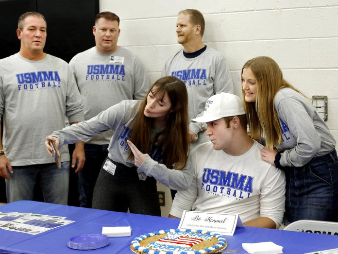 Photo - Bo Kemmet's older sister,  Kate, takes a picture of herself, Bo and their younger sister, Meg, 14, at his reception table after  he signed to play football with United States Merchant Marines Academy during Signing Day event at Norman North High School on Wednesday, Feb. 6, 2019.  Their dad is in background, at far left. Photo by Jim Beckel, The Oklahoman.