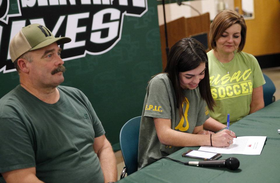 Photo - Sydney Arneson signs to play soccer for USAO next to her parents Sharon and Gary during signing day ceremony at Edmond Santa Fe High School in Edmond, Okla., Wednesday, Feb. 6, 2019. Photo by Sarah Phipps, The Oklahoman