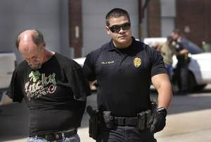 photo - Shawnee patrolman A. Bizzell brings a suspect into the vo-tech center to be processed while a fellow officer removers another suspect from a patrol car in the background. Law enforcement personnel representing various municipal, county and state agencies spread out across multiple counties in central Oklahoma to arrest up to 40 individuals in a sweep that officials said targeted a substantial methamphetamine distribution network on Wednesday, June 27, 2012. Suspects were brought to the Gordon Cooper Vocational-Technical Center where they were processed before being taken to jail. Photo by Jim Beckel, The Oklahoman