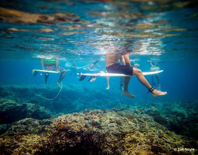 Underwater image by Zak Noyle of surfers waiting to catch a wave.
