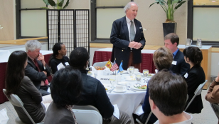 McCall Smith (standing) had lunch with HAI researchers, students and supporters.