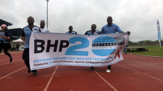 Botswana Harvard Partnership banner carried by runners.