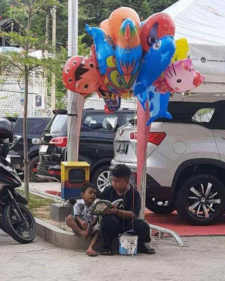 132627906 440680777306129 6109869143963869749 n - Niño le enseña a leer a su hermano menor mientras vende globos en la calle. Sobreviven de a dos