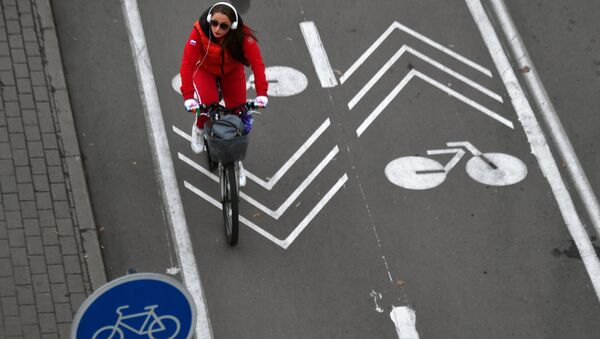 The girl rides a bicycle along the road in Moscow. Archive photo